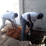 Mixing compost (animal dung, peanut shells and saw dust)